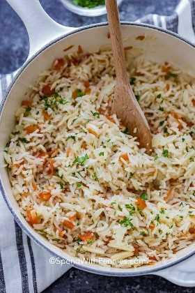 Una olla llena de arroz pilaf se agita con una cuchara de madera.