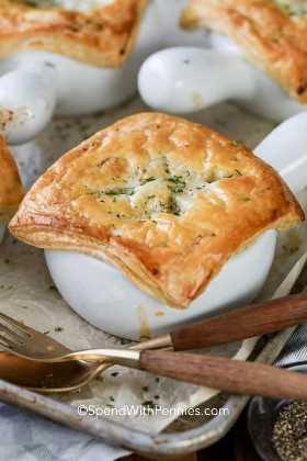 Un plato blanco lleno de pastel de pollo en una bandeja para hornear con utensilios de madera.