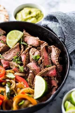 ¡Este aderezo para fajita de bistec está hecho con aceite de oliva, jugo de naranja, jugo de limón, ajo y hierbas y especias sabrosas que dan como resultado fajitas tiernas y jugosas!