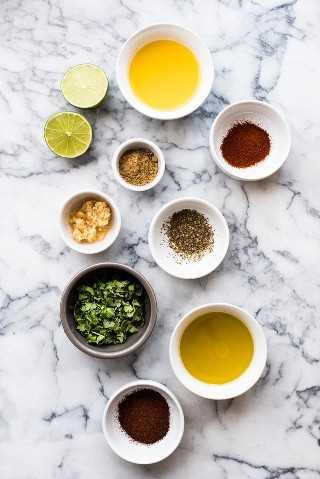 Ingredientes de marinada de fajita de bistec en una mesa: aceite de oliva, jugo de limón, jugo de naranja, ajo, orégano, comino, pimentón ahumado y cilantro.