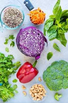 La quinoa tricolor cocida, la col roja, los palitos de zanahoria, la albahaca, el cilantro, el brócoli y un pimiento rojo como los ingredientes para la mejor receta de ensalada de quinua.