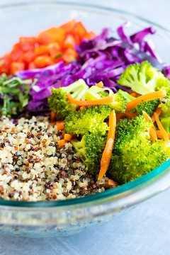 Quinoa tricolor, brócoli, repollo y pimientos rojos en un recipiente de vidrio.