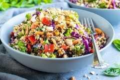 Receta tailandesa de la ensalada de la quinoa del cacahuete en dos cuencos grises con cilantro en el fondo.