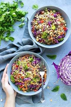 Una mano que sostiene un cuenco lleno de una ensalada sana de la quinoa.
