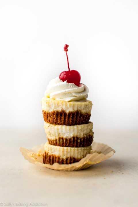 ¡Hornee pasteles de queso cremosos individuales en una sartén para muffins! Esta receta produce 9 mini cheesecakes. Receta en sallysbakingaddiction.com