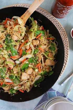 sobre la cabeza de pollo chow mein con un utensilio de madera en una sartén negra con condimentos en platos blancos en el fondo