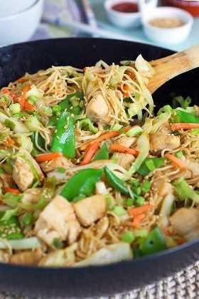 pollo chow mein con un utensilio de madera en una sartén negra con condimentos en platos blancos al fondo