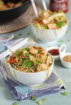 pollo chow mein en un tazón blanco, colocado sobre una toalla azul, con otro tazón de pollo chow mein, condimentos en recipientes blancos y una sartén negra rellena con chow meain en el fondo