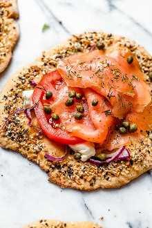Estas pizzas para el desayuno, que son geniales para el desayuno, el almuerzo o el desayuno para la cena, combinan dos de mis comidas favoritas: lox, la masa de pizza y todo el condimento de bagel.