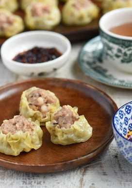 Shumai con relleno de cerdo en un plato de madera con salsa de ajo chili y una taza de té en el lado