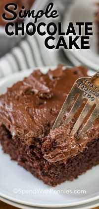 Una rebanada de pastel de chocolate con glaseado de chocolate está en un plato blanco con un tenedor que le da un mordisco.