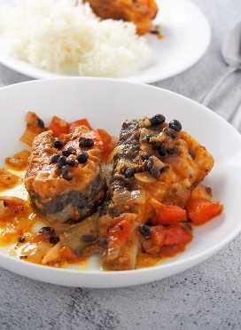 bangus con tausi y tomates en un plato blanco con arroz al vapor