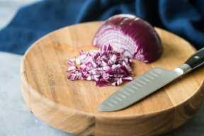 Cortar la cebolla roja en una tabla para cortar madera.