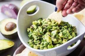 Sumergir un chip de tortilla en un plato de guacamole saludable.