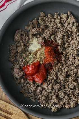Una sartén de carne molida cocida con condimento para tacos y tomate encima para hacer carne para tacos