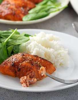 salmón a la parrilla con glaseado hoisin en un plato blanco con arroz al vapor y espinacas frescas