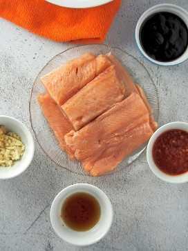 filetes de salmón crudo en una bandeja transparente con ingredientes de marinada hoisin en el lado