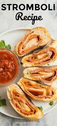 Rebanadas de esta sencilla receta de Stromboli sentadas en un plato blanco y rodeando un tazón claro de salsa