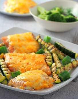 Salmón al horno con Sweet Chili-Mayo Topping en una fuente blanca con calabacín a la parrilla