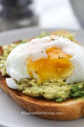 Un huevo escalfado con la yema de huevo rota sobre una tostada de aguacate.