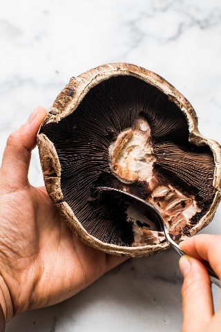 Eliminar las branquias de los hongos portabello para hacer tacos de champiñones vegetarianos