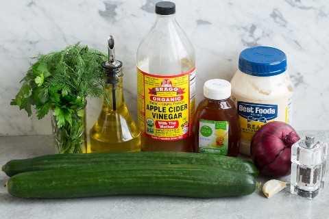 Los ingredientes necesarios para hacer la ensalada de pepino que se muestra aquí incluyen los pepinos ingleses, la mayonesa, el aceite de oliva, el ajo, el vinagre de manzana, el eneldo, el perejil, la miel y la cebolla roja.