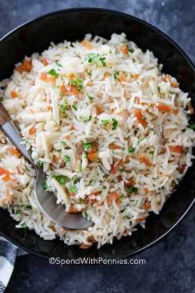 Un tazón de servir negro lleno de arroz pilaf con una cuchara de plata.