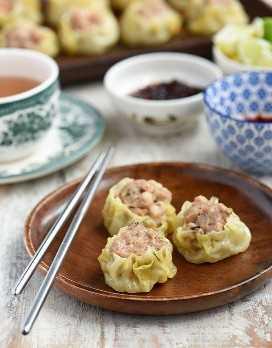 Siomai de cerdo en un plato de madera con una taza de té, salsa de chile y salsa de acompañamiento