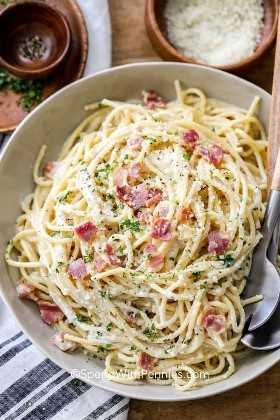 Un tiro de espagueti carbonara con una cuchara de madera, queso parmesano y pimienta.