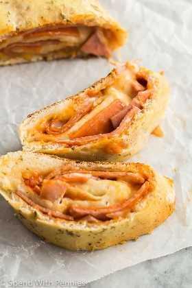 Close up de 3 rebanadas de receta de stromboli con jamón, pepperoni y salami con queso