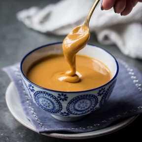 Colher de doce de leite caseiro de uma tigela azul estampada.