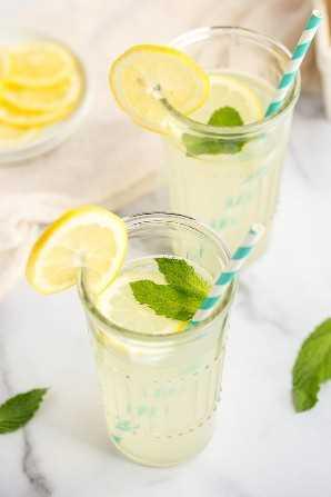 Dos vasos de limonada con rodajas de limón, hojas de menta y pajitas.