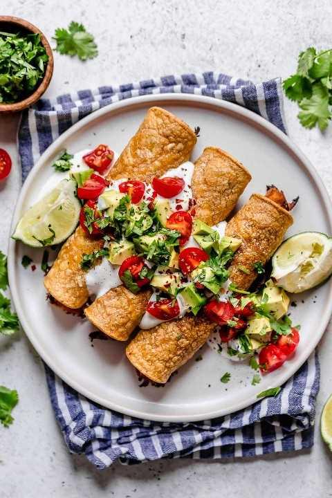 Taquitos en un plato blanco cubierto con crema agria, tomates, aguacates y cilantro. Las cuñas de limón se colocan a un lado y la placa se coloca en una servilleta con rayas azules.