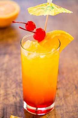Tequila Sunrise Cocktail com laranja, cerejas e um guarda-chuva.