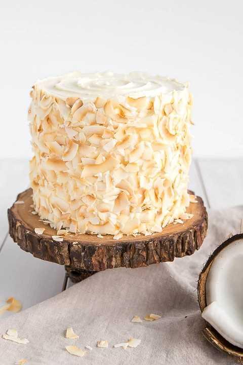 Esta receta de pastel de coco, húmeda y deliciosa, está impregnada de sabor a coco natural y decorada con copos de coco tostado gigante. | livforcake.com