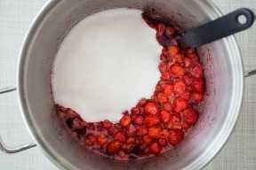 Agregar el azúcar a una olla de mermelada de fresa casera.
