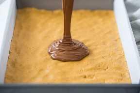 Verter el chocolate derretido sobre barras de mantequilla de maní.