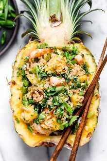 El arroz frito con camarones y piña tiene una deliciosa combinación de sabores salados, dulces y picantes. ¡Sírvelo en piñas ahuecadas para una presentación hermosa!