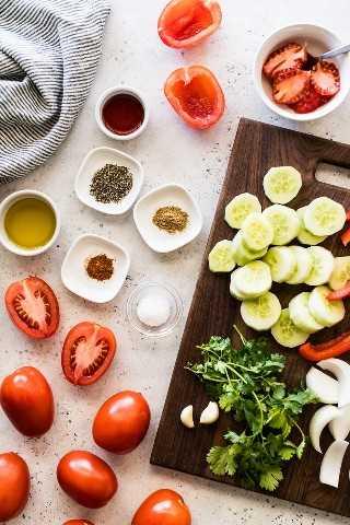 Ingredientes para gazpacho sobre una mesa blanca y azul. Incluye tomates, pepinos, especias, aceite de oliva, ajo, cebolla, pimientos rojos y vinagre de vino tinto.