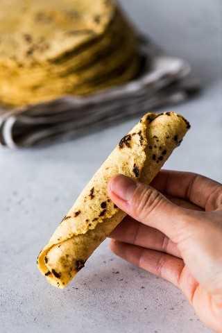 Tortilla de maíz enrollada que se sostiene en una mano.