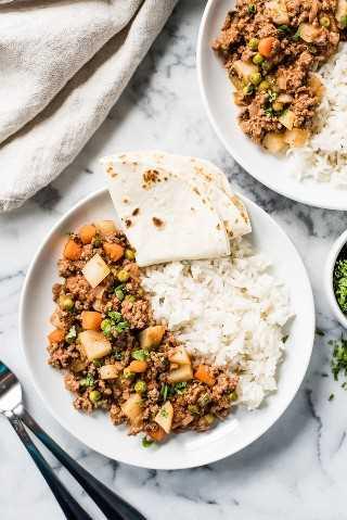 Picadillo en un plato con arroz blanco y una tortilla de harina.