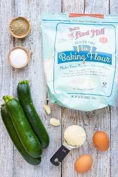 Abobrinha, farinha, ovos, queijo parmesão como ingredientes para uma receita de bolinho de abobrinha.