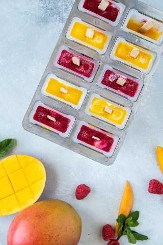 Paletas de yogur de mango y frambuesa en paletas.