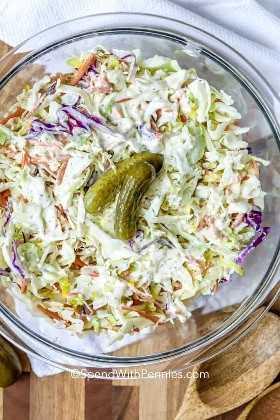 Un plato de ensalada de col encurtido cubierto con pepinillos.