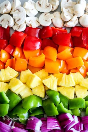Un arcoiris de verduras en una sartén para kebabs de pollo.