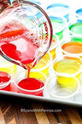 As doses de gelatina foram alinhadas em uma assadeira e a mistura de gelatina foi vertida sobre elas.