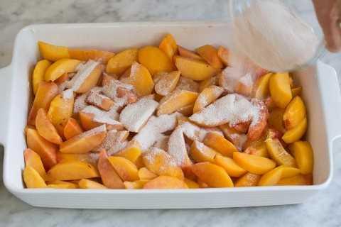Verter la mezcla de azúcar sobre los duraznos en una fuente para hornear.