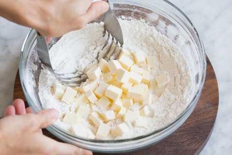 Cortar la mantequilla en la mezcla de harina en un tazón de vidrio con un cortador de pastelería.