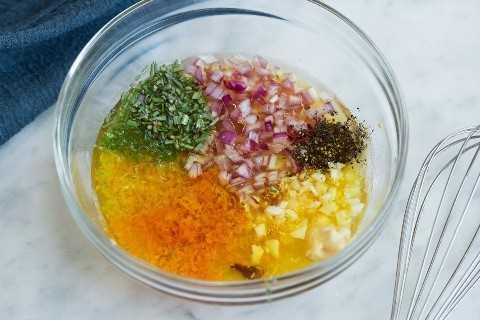 Mostrando cómo hacer la marinada de pollo con cítricos. Ingredientes en un bol de vidrio con batidor a un lado.