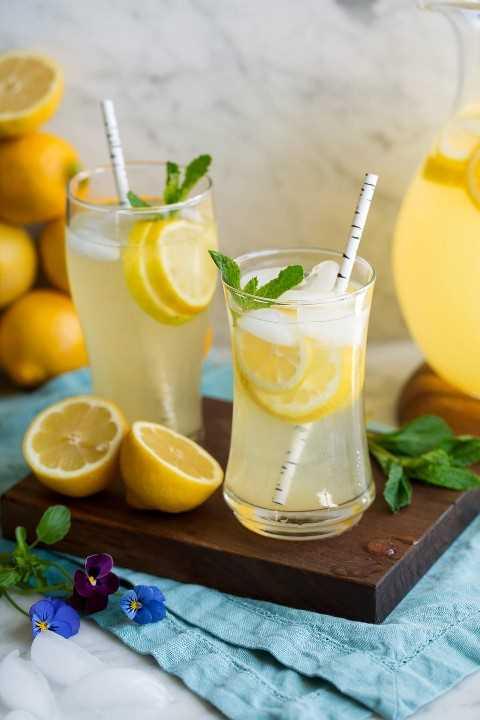 Dos vasos de limonada en una bandeja de madera.